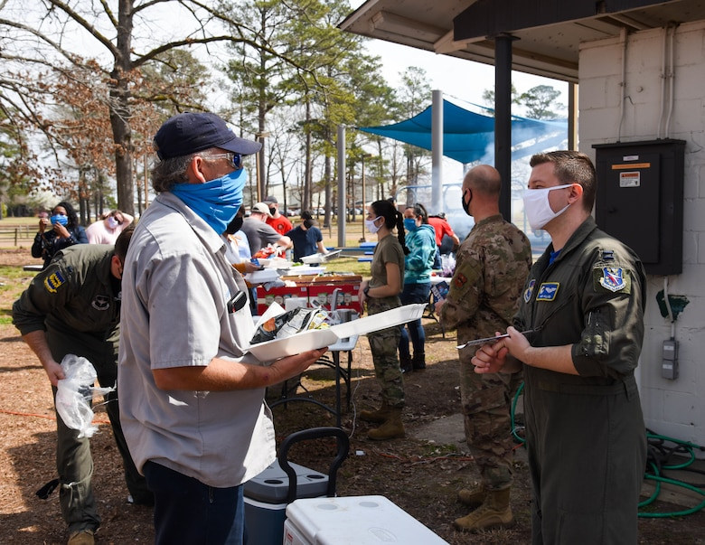 "Two 14th Flying Training Wing members discuss the Air Force Assistance Fund on March 12, 2021, at Columbus Air Force Base, Miss. Columbus AFB hosted a ""Burger Burn"" to kick-off the 2021 season of the AFAF. (U.S. Air Force photo by Sharon Ybarra)"