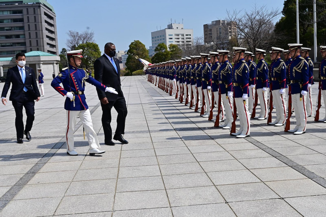 A soldier escorts a man in front of a military formation.