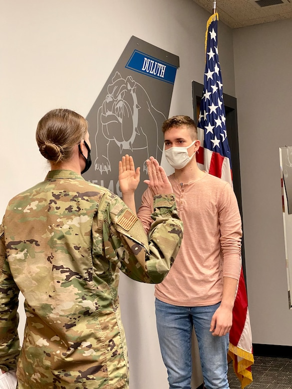 Capt. Mylii Pukema administers the Oath of Office to her nephew, Joey Gigliotti on March 15, 2021. Gigliotti is the third generation of his family to serve at the 148th Fighter Wing, Minnesota Air National Guard. (U.S. Air National Guard photo by Audra Flanagan)