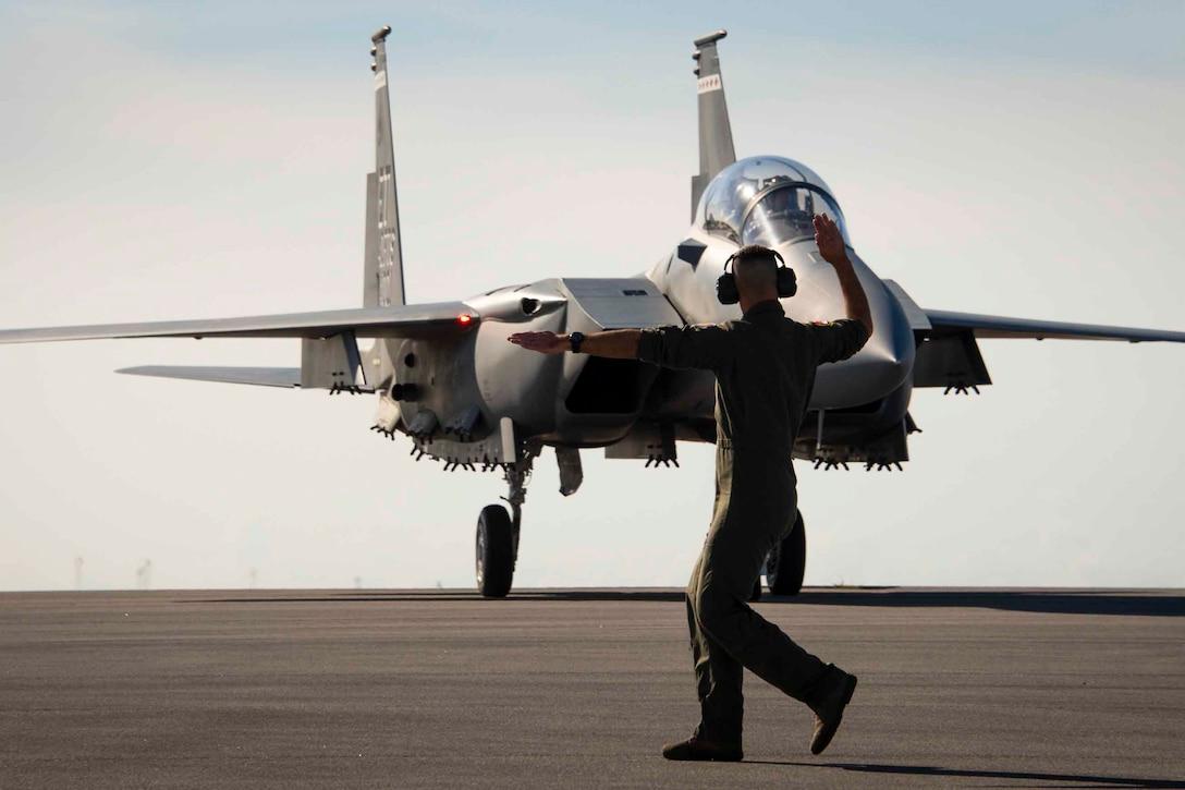 An airman signals at an aircraft.