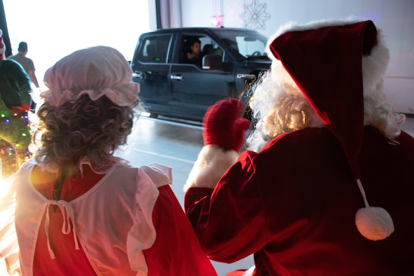 """Children's smiles and loud Santa """"thank-yous"""" were seen and heard through the car windows as families drove through a winter wonderland display at the 168th Wing. Volunteers from different squadrons built holiday scenes for the children to celebrate as a part of a wing competition, December 12, 2020. The wing holiday celebration was held a little differently this year with masks and social distancing and still brought joy despite COVID-19. (U.S. Air National Guard photo by Senior Master Sgt. Julie Avey)"""