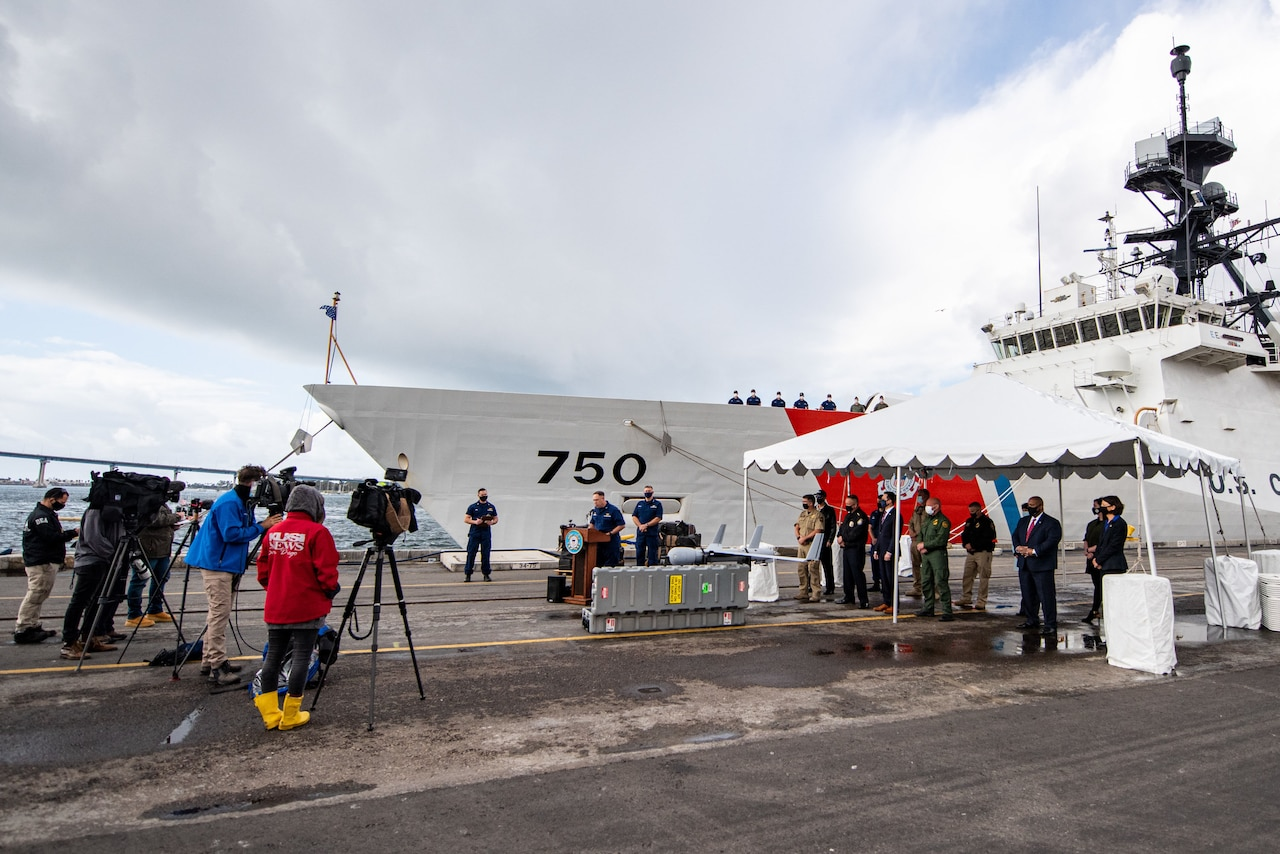 A man stands at a lectern set up outside and speaks to news crews gathered on a pier; a large ship is docked in the background.
