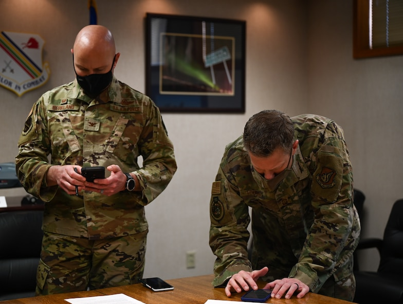 U.S. Air Force Col. David Berkland, the 354th Fighter Wing commander, and Chief Master Sgt. John Lokken, make a donation to the Air Force Assistance Fund (AFAF) via a mobile device on Eielson Air Force Base, Alaska, March 15, 2021.