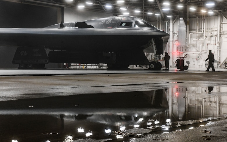 """U.S. Air Force Senior Airman Tony Nogales, left, and Airman 1st Class Byron Humphrey, 509th Aircraft Maintenance Squadron crew chiefs, conclude preflight checks in support of a Bomber Task Force at Whiteman Air Force Base, Missouri, March 16, 2021. The B-2 Spirit's low-observable, or """"stealth,"""" characteristics give it the ability to penetrate an enemy's most sophisticated defenses and threaten its most-valued, heavily defended targets while avoiding adversary detection, tracking and engagement. Its participation in recurring Bomber Task Force operations and engagements with our allies and partners demonstrate and strengthen our shared commitment to global security and stability. (U.S. Air Force photo by Staff Sgt. Sadie Colbert)"""