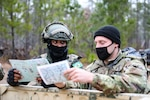 Two soldiers hold maps in their hands and talk.