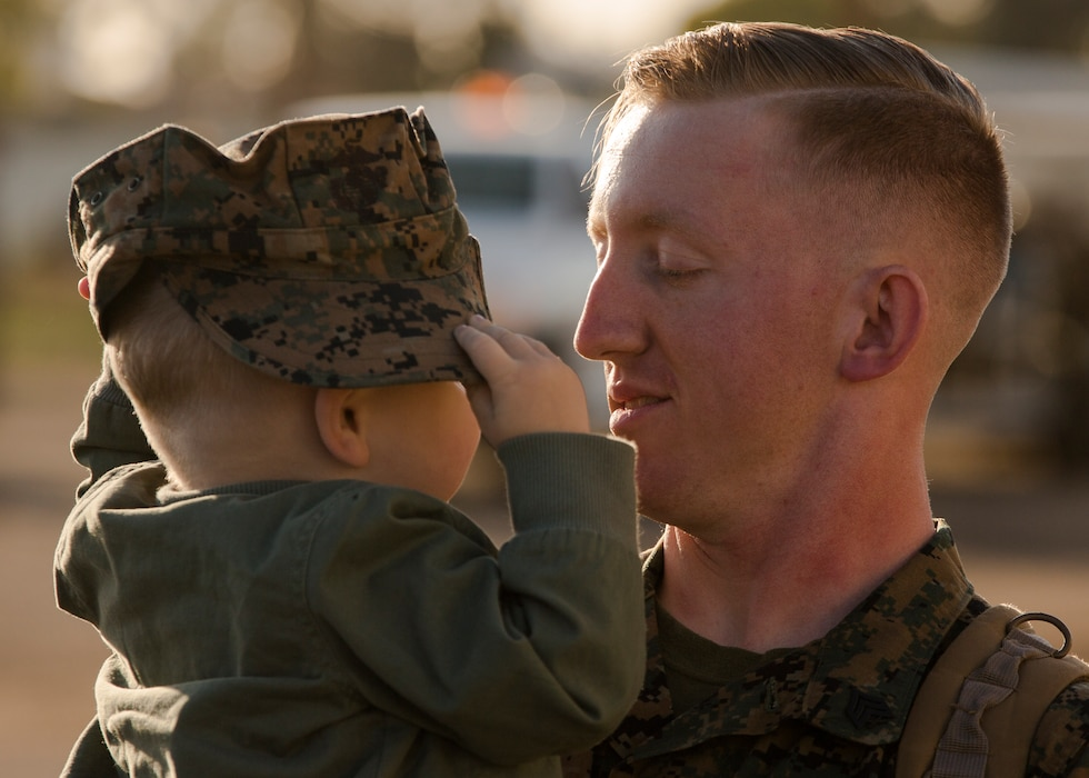 A U.S. Marine with Marine Fighter Attack Squadron (VMFA) 323 greets his family upon his return to MCAS Miramar from a 10-month carrier deployment, Feb. 26, 2021. VMFA-323 completed their last deployment while flying the F/A-18 Hornet and will be transitioning to flying the F-35 Lightning II. (U.S. Marine Corps photo by Lance Cpl. Levi Voss)