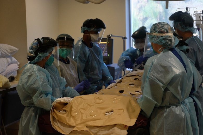 U.S. Air Force Staff Sgt. Minh Tran, third from the left, a medical technician assigned to COVID Theater Hospital-1, and his civilian colleagues prepare to move a patient at Los Angeles County + University of Southern California Medical Center, Los Angeles, Calif., August 10, 2020.  Tran is a member of a medical support team deployed from the 60th Medical Group, Travis Air Force Base, Calif., which integrated with hospital staff to provide additional medical support. U.S. Northern Command, through U.S. Army North, remains committed to providing flexible Department of Defense support to the Federal Emergency Management Agency in support of the whole-of-America COVID-19 response. (U.S. Army photo by Lt. Col. Charles Calio)