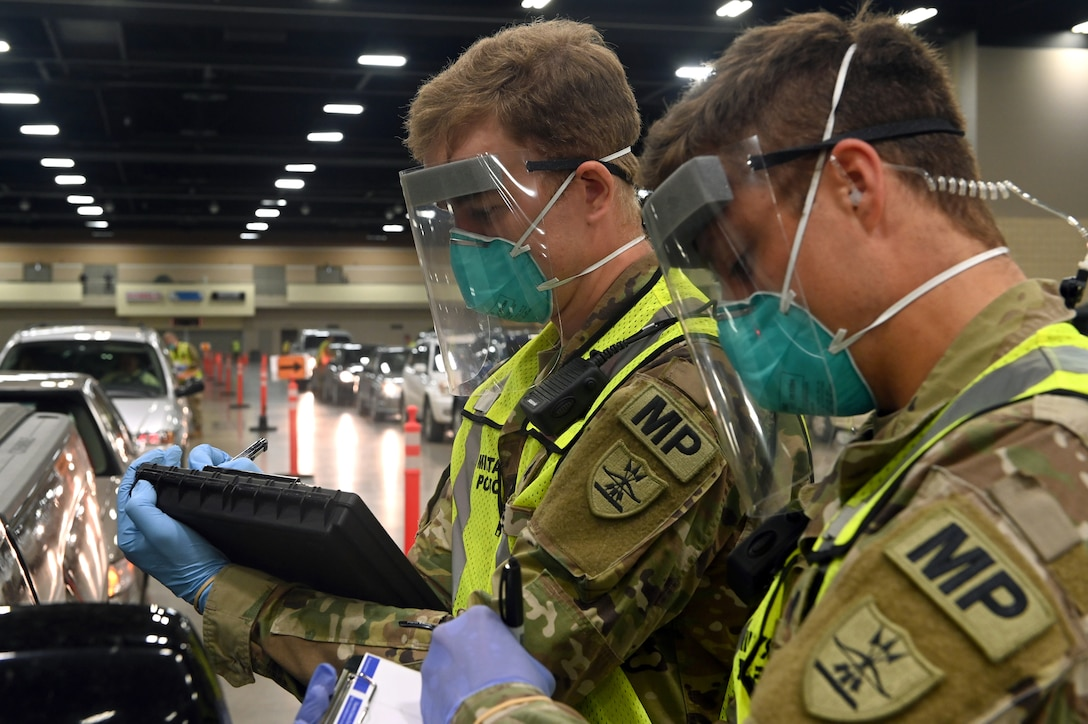Sgt. Chase Bode, left, and Spc. Isaac Bolton of the 816th Military Police Company, North Dakota National Guard, collect data at the COVID-19 mobile testing site inside the Bismarck Event Center in Bismarck, North Dakota, May 2, 2020. The NDNG marked the one-year anniversary of its support of the pandemic response March 16, 2021.
