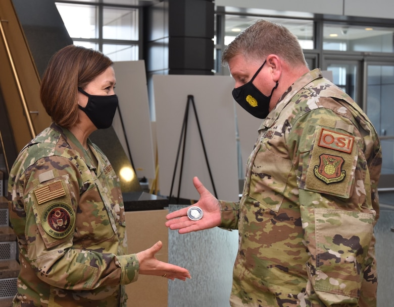 Office of Special Investigations Commander, Brig. Gen. Terry L. Bullard, presents his coin to Chief Master Sergeant of the Air Force JoAnne S. Bass, during her inaugural visit to OSI Headquarters March 12 as 19th CMSAF, and the first woman in history to serve as the highest-ranking noncommissioned officer of a U. S. military service branch. (Photo by SA Spencer King)