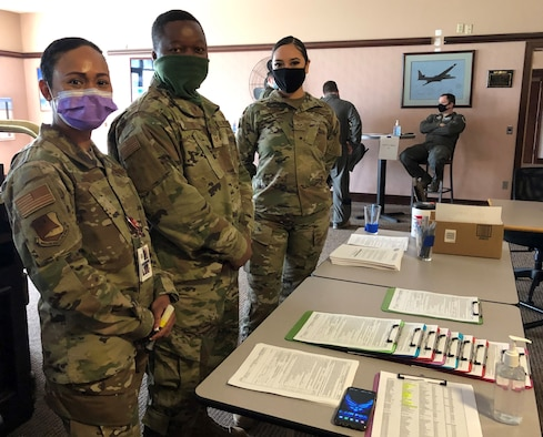 Senior Master Sgt. Ellie Torres, 940th AMDS/SGO, Staff Sgt. Blee Toe, AMDS/AMDS and SrA. Melanie Ortega, AMDS/SGSP  greet the voluntary participants at the Recce Point Club first, before processing through the line for the COVID-19 vaccine.