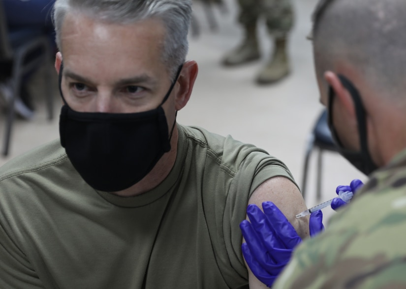 """Army Col. John J. Herrman, the commander of Area Support Group-Kuwait, looks away as he receives his Janssen Biotech COVID-19 vaccine at the March 13, 2021 rollout of Operation Med Spear at Camp Arifjan, Kuwait. """"It is one of our highest priorities here at ASG-Kuwait,"""" Herrman said. """"Without the vaccine, all we're going to do is continue to go up and down in terms of COVID-19 spikes."""" (U.S. Army photo by Staff Sgt. Neil W. McCabe)"""