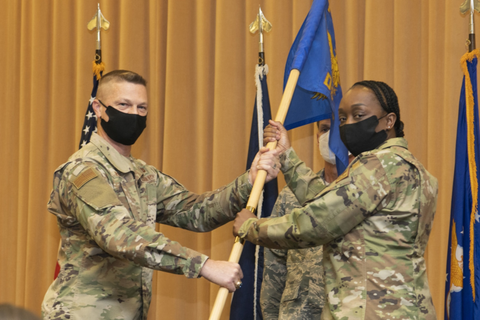 An airman hands a flag to another during a change of command ceremony