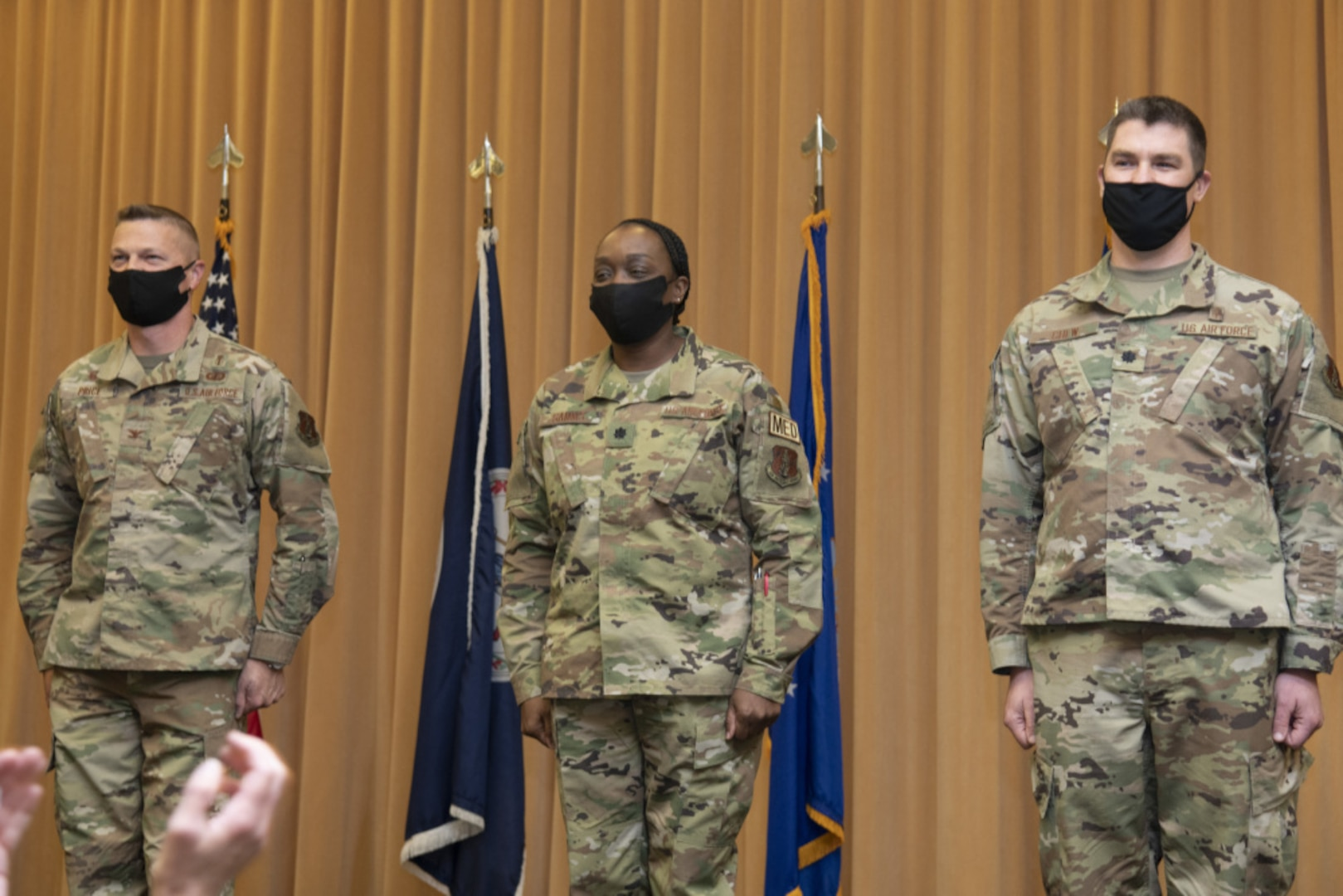 Three Airmen stand at attention in front  of flags