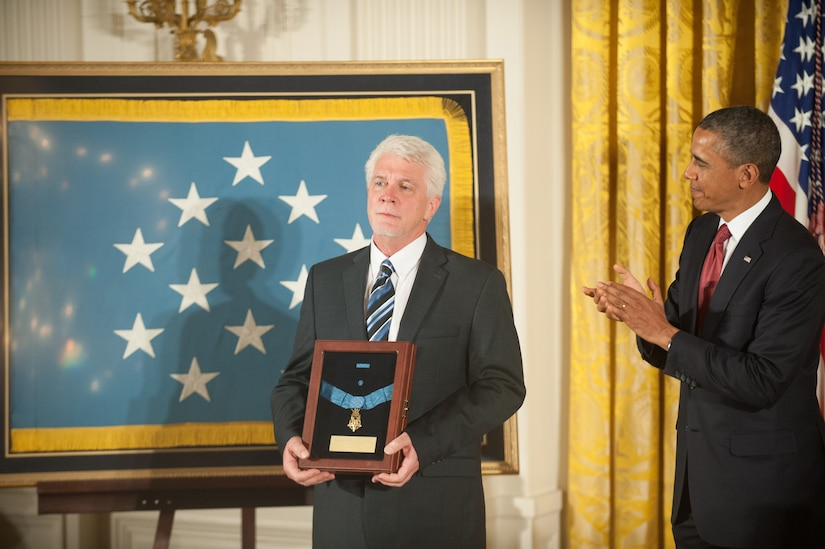 A man holds a shadow box with a medal as another man applauds beside him.