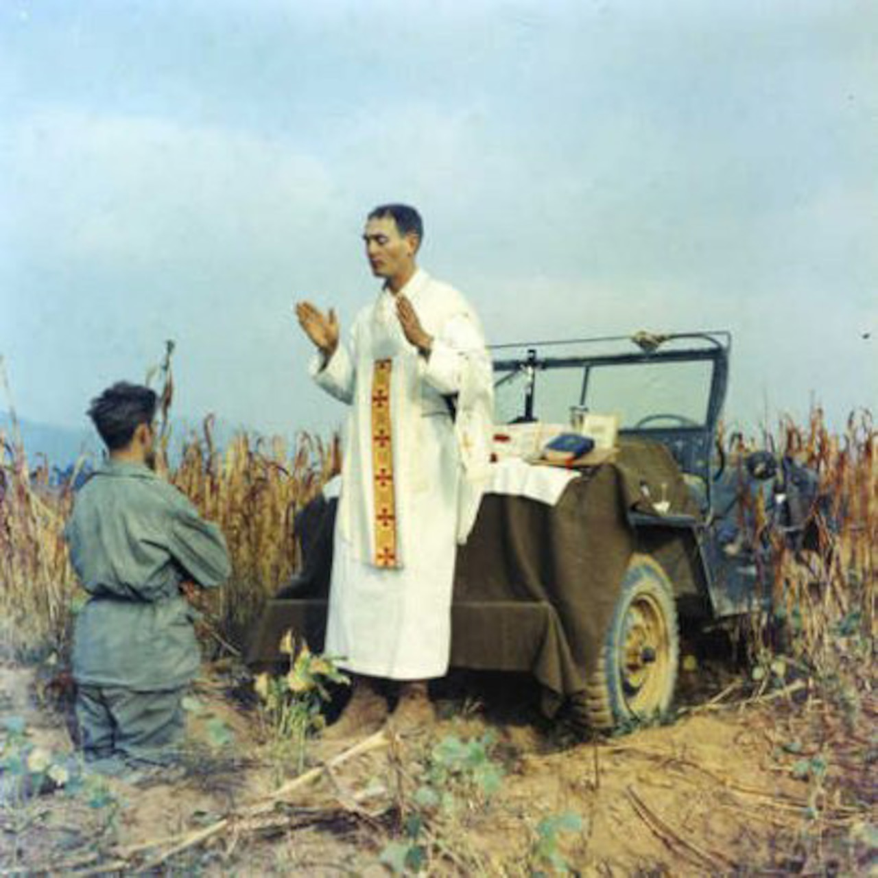 A priest blesses a kneeling man beside a Jeep in a field.