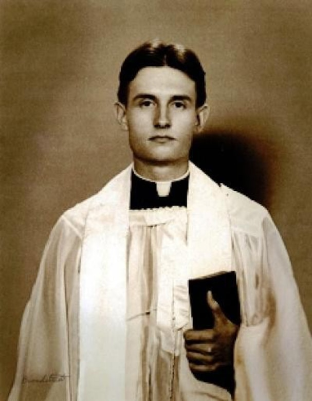 A man in liturgical dress holds a Bible.
