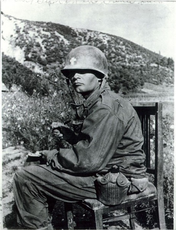 A man in combat dress looks out from under a helmet while writing a letter. The helmet has the insignia of a cross indicating that he is a clergyman.