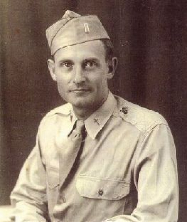 A young man in military shirt, tie and cap looks at the camera.