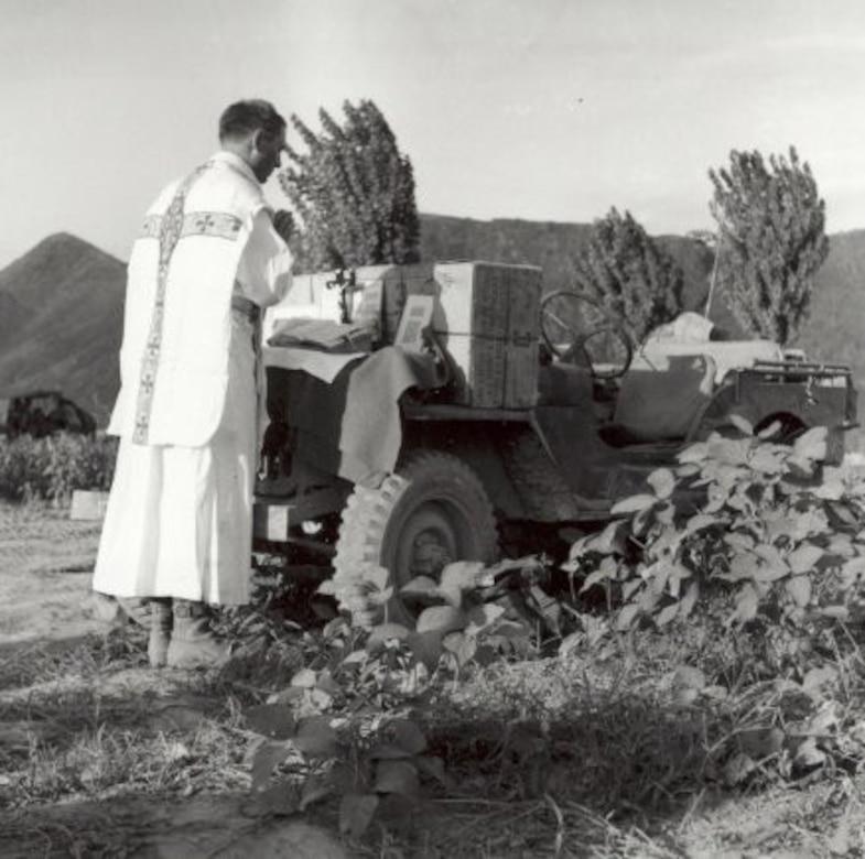 A priest prays toward an outdoor altar built on a Jeep.