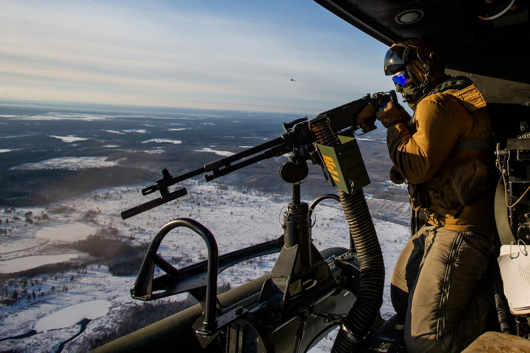 Corporal Lake M. Keating, a UH-1Y Huey crew chief, fires an M240B machine gun at Alpena Combat Readiness Training Center, Michigan, January 25, 2021. Marines with Marine Light Attack Helicopter Squadron 167 (HMLA-167) trained with soldiers from the Michigan Air National Guard to conduct expeditionary operations in a cold weather environment. HMLA-167 is a subordinate unit of 2nd Marine Aircraft Wing, which is the air combat element of II Marine Expeditionary Force. (U.S. Marine Corps photo by Lance Cpl. Elias E. Pimentel III)