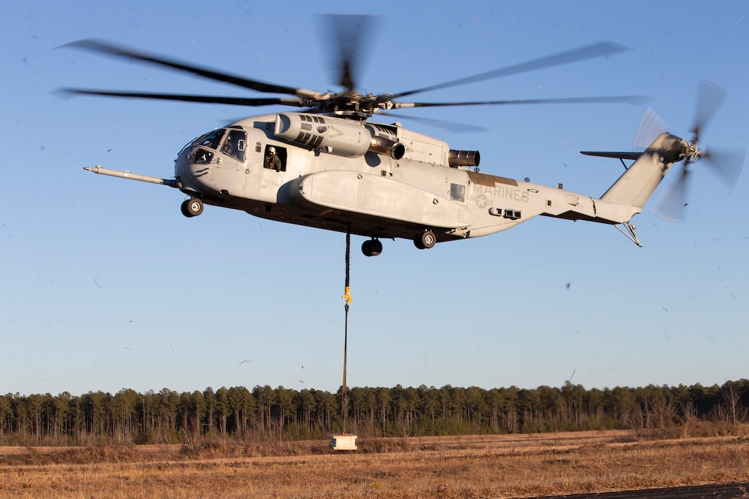 """A CH-53K """"King Stallion"""" conducts an external lift of a 4,000 pound concrete block at Marine Corps Outlying Field Camp Davis, North Carolina, Feb. 3, 2021. Marine Operational Test and Evaluation Squadron One (VMX-1) tested the CH-53K's heavy lifting capabilities in order to enhance their skills and proficiency with cargo movement and operations. The CH-53K will replace the CH-53E """"Super Stallion,"""" which has served the Marine Corps for 40 years, and will transport Marines, heavy equipment and supplies during ship-to-shore movement in support of amphibious assault and subsequent operations ashore.  (U.S. Marine Corps photo by Cpl. Damaris Arias)"""