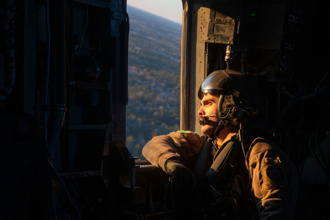 Staff Sgt. Joshua Milne looks out the port window of a CH-53E while in flight at Marine Corps Air Station New River, North Carolina, Feb. 3, 2021. Marine Heavy Helicopter Squadron 464 (HMH-464) were refueled by a KC-130J, which offers a 60,000 pound fuel capacity that it can allocate between its own offload capacity using its wing and external tanks while in the air. HMH-464 is a subordinate unit of 2nd Marine Aircraft Wing, which is the aviation combat element of II Marine Expeditionary Force. (U.S. Marine Corps photo by Lance Cpl. Caleb Stelter)