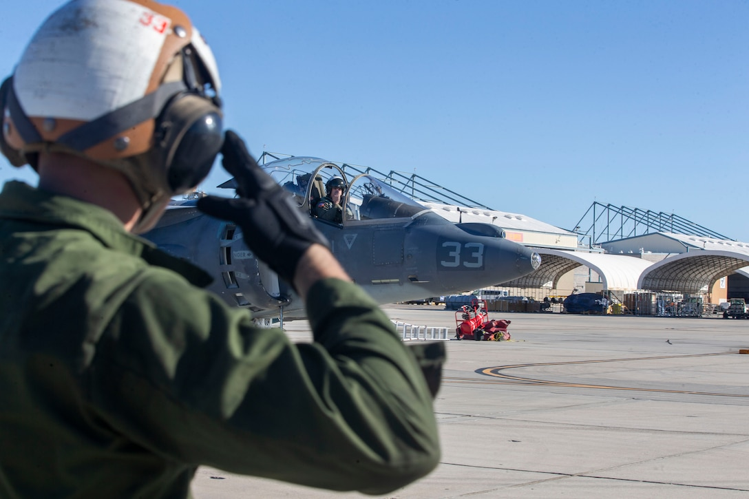 Lance Cpl. Carson Batterton, a fixed-wing aircraft mechanic, salutes the pilot of an AV-8B Harrier II as he departs the staging area at Marine Corps Air Station Yuma, Arizona, Feb. 18, 2021. Marines with Marine Attack Training Squadron 203 (VMAT-203) trained with ordnance in an unfamiliar environment in order to increase proficiency in critical mission skills such as low altitude tactics, complex maneuvers, and close air support. VMAT-203 is a subordinate unit of 2nd Marine Aircraft Wing, the aviation combat element of II Marine Expeditionary Force. (U.S. Marine Corps photo by Sgt. Servante R. Coba)