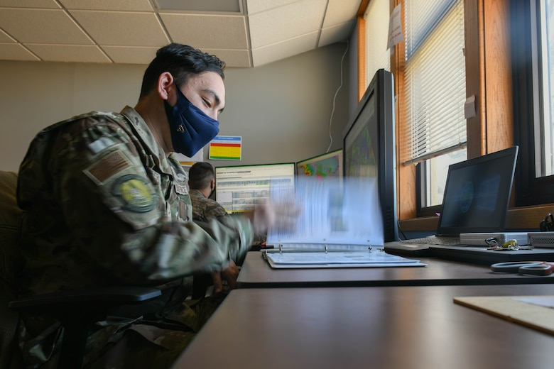 Airman 1st Class Kyle Carpenter, 22nd Operations Support Squadron weather forecaster, looks through forecast reference material March 3, 2021, at McConnell Air Force Base, Kansas. The reference material is made up of meteorological techniques based on season specific weather regimes over the United States. It also contains local forecasting techniques based on topography and effects particular weather systems have on McConnell AFB. (U.S. Air Force photo by Senior Airman Nilsa Garcia)