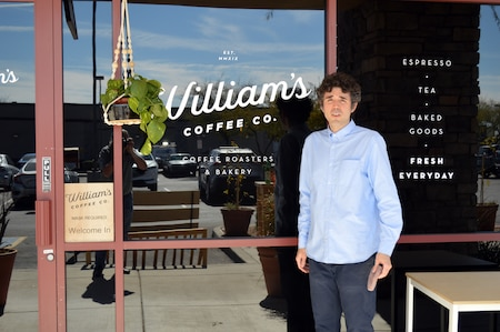man in blue shirt standing in front of store front window of a coffee shop.