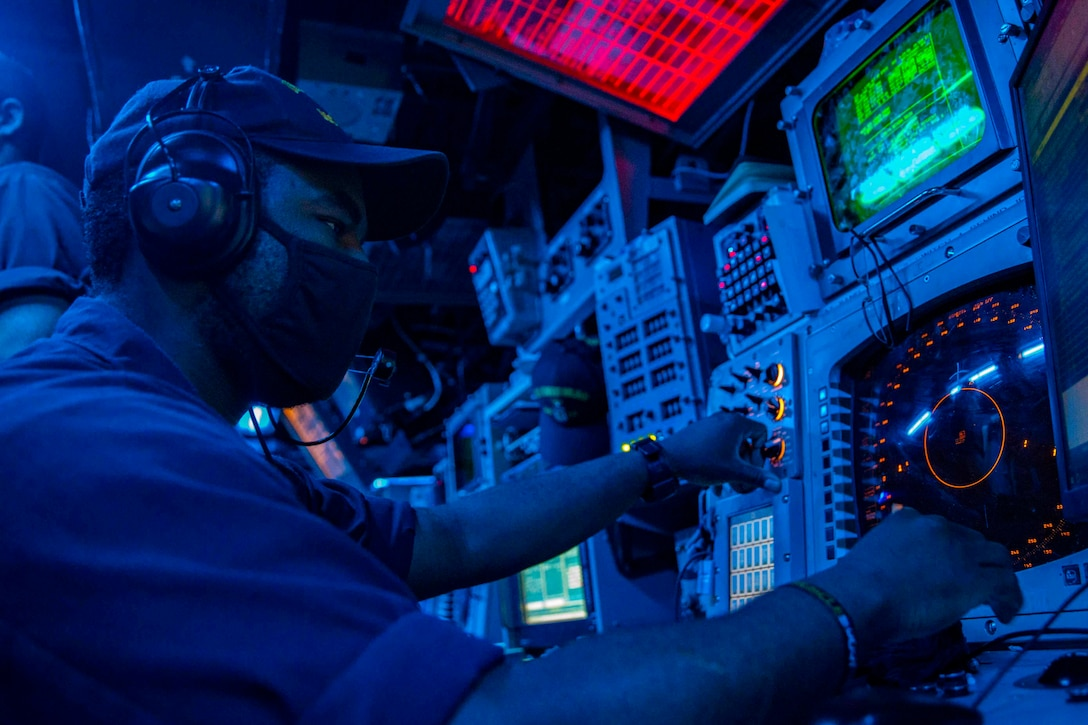 A sailor illuminated by blue light sits in front of digital monitors.