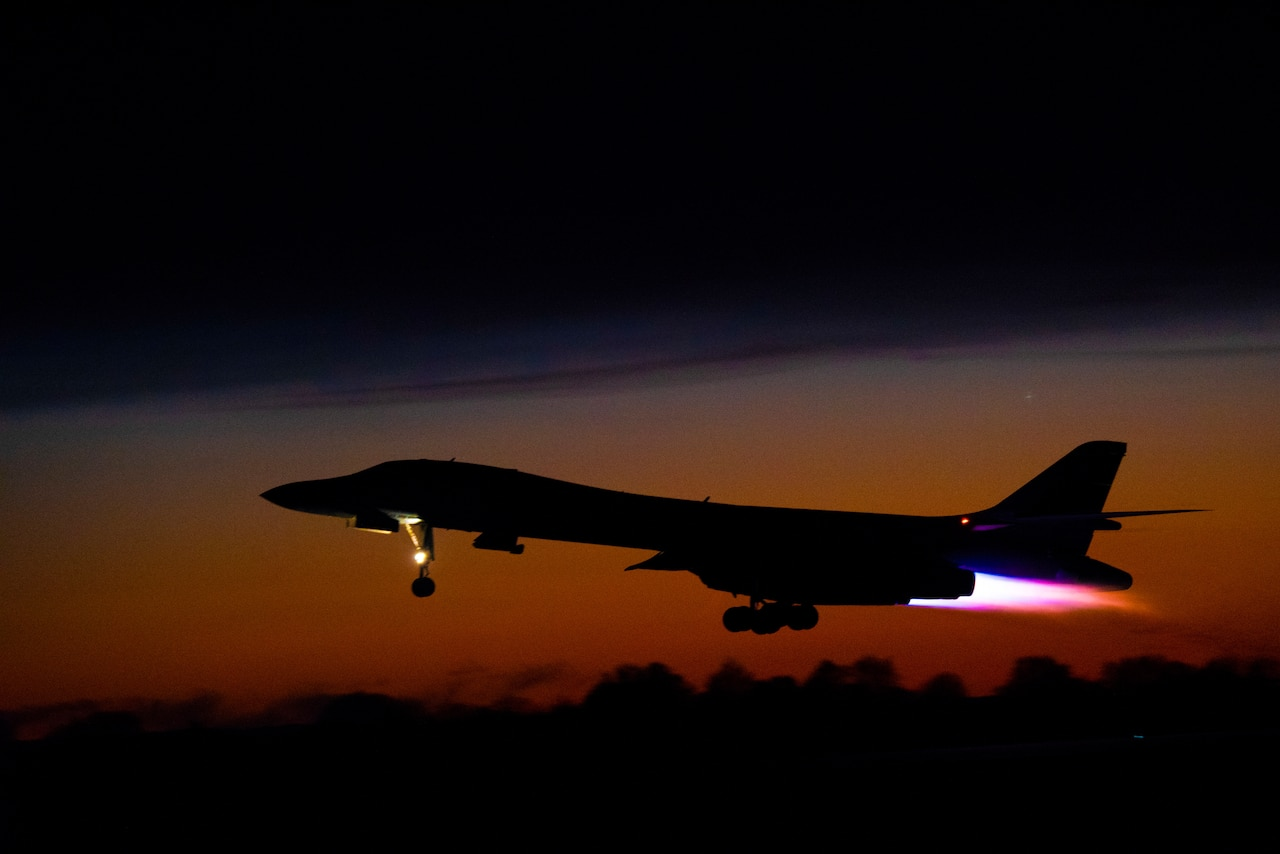 A B-1B Lancer aircraft takes off in front of a sunset.