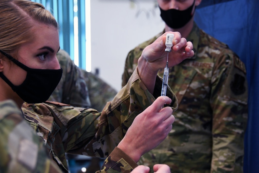 A soldier wearing a face mask holds a syringe while inserting the needle into a vial.
