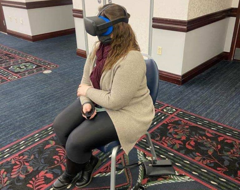 Contract specialist experiences virtual reality suicide prevention training with VR goggles and a controller.