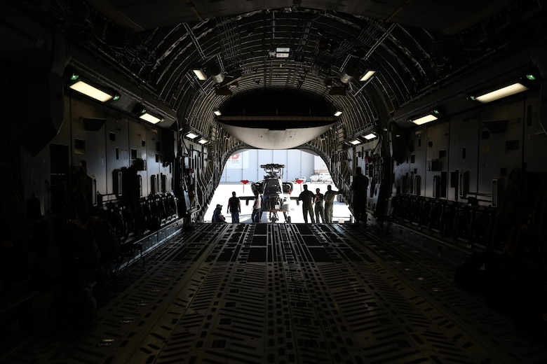 Members of the Arizona National Guard's 161st Air Refueling Wing, the Royal Air Force, and The Boeing Company load an AH-64 Apache helicopter into a Royal Air Force C-17 Globemaster III, at the Goldwater Air National Guard Base in Phoenix, Arizona Jan. 21, 2021. The 161st was contacted by the U.S. Army's Apache foreign military sales program office to help load the attack helicopters on C-17 aircraft for shipment to the UK, due to its secure ramp space for the project, and qualified air transportation specialists who can process complex air cargo ensuring safety of flight during air transport.  (U.S. Army National Guard photo by Spc. Thurman Snyder)
