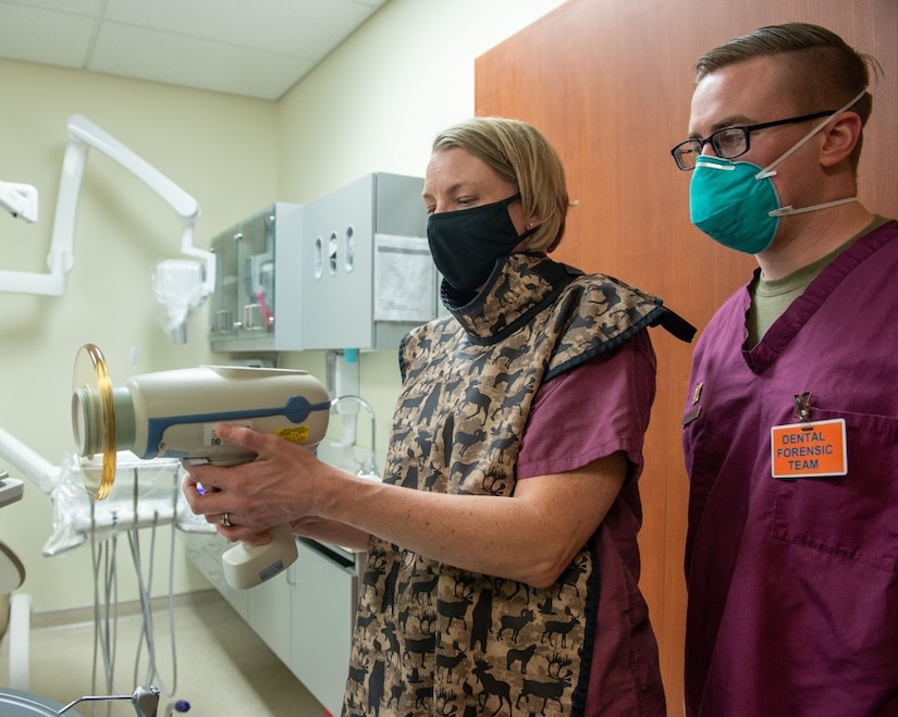 U.S. Air Force Capt. Ryan Zarnowski, right, a general dentist assigned to the 673d Dental Squadron, teaches U.S. Air Force Col. Kirsten Aguilar, Joint Base Elmendorf-Richardson and 673d Air Base Wing commander, how to operate an X-ray unit at JBER, Alaska, March 2, 2021.