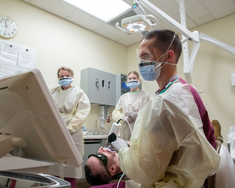 U.S. Air Force Senior Airman Regan Bassett, front, a dental technician assigned to the 673d Dental Squadron, performs a dental scan on U.S. Air Force Chief Master Sgt. Lee Mills, Joint Base Elmendorf-Richardson and 673d Air Base Wing command chief, during a 673d Dental Squadron immersion tour at Joint Base Elmendorf-Richardson, Alaska, March 2, 2021.
