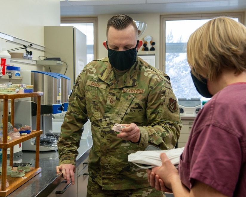 U.S. Air Force Master Sgt. Matthew Garcia, left, a dental lab technician assigned to the 673d Dental Squadron, shows fabricated crowns to U.S. Air Force Col. Kirsten Aguilar, Joint Base Elmendorf-Richardson and 673d Air Base Wing commander, at JBER, Alaska, March 2, 2021.