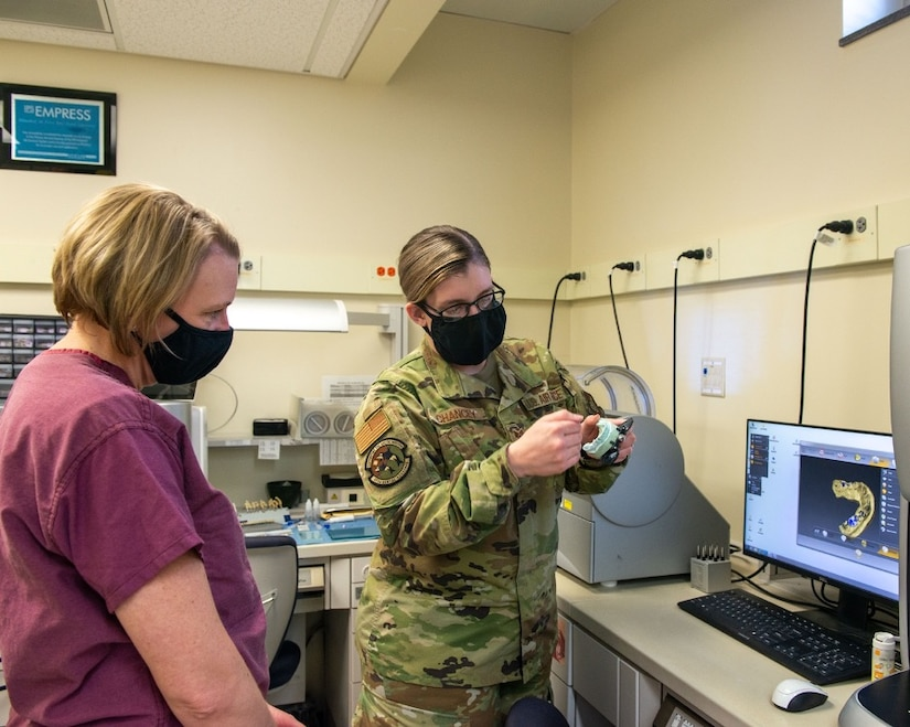 U.S. Air Force Staff Sgt. Aimee Chancey, right, a dental laboratory technician assigned to the 673d Dental Squadron, shows a model camera for crowns and implants to U.S. Air Force Col. Kirsten Aguilar, Joint Base Elmendorf-Richardson and 673d Air Base Wing commander, at JBER, Alaska, March 2, 2021.