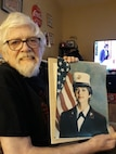 """Lt. Col. Sally Ann Falco's father, Kenneth Townes, holds a photo of Falco taken while she was at recruit training in 1987 at Marine Corps Recruit Depot Parris Island, South Carolina. Falco served as an enlisted Marine for 14 years before her acceptance to the Meritorious Commissioning Program. She commissioned in August 2001 and will soon retire after 34 fruitful years in the Marine Corps. """"I've just been privileged to be allowed to be a Marine,"""" Falco said. """"I still love it as much as the day I came in, and I would stay in forever, but I want to make room for others to climb the ladder and at the same time, contribute to society in another capacity."""" (Courtesy photo by Falco's mother, Loretta """"Tootsie"""" Townes)"""