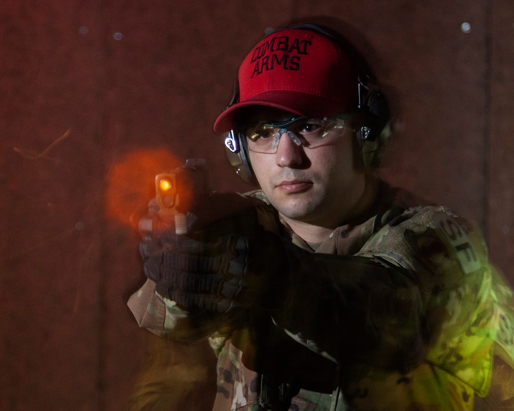 Air Force Technical Sgt. Richard Thomas, the 88 Security Forces Squadron noncommissioned officer in charge of Combat Arms, is captured firing the M18 pistol with a remote camera on the indoor range at Wright-Patterson Air Force Base, Ohio, on Feb. 17, 2021. Thomas and his team of combat arms trainers work to keep personnel in the 88th Air Base Wing weapons qualified for readiness and deployment requirements. (U.S. Air Force photo by Ty Greenlees)