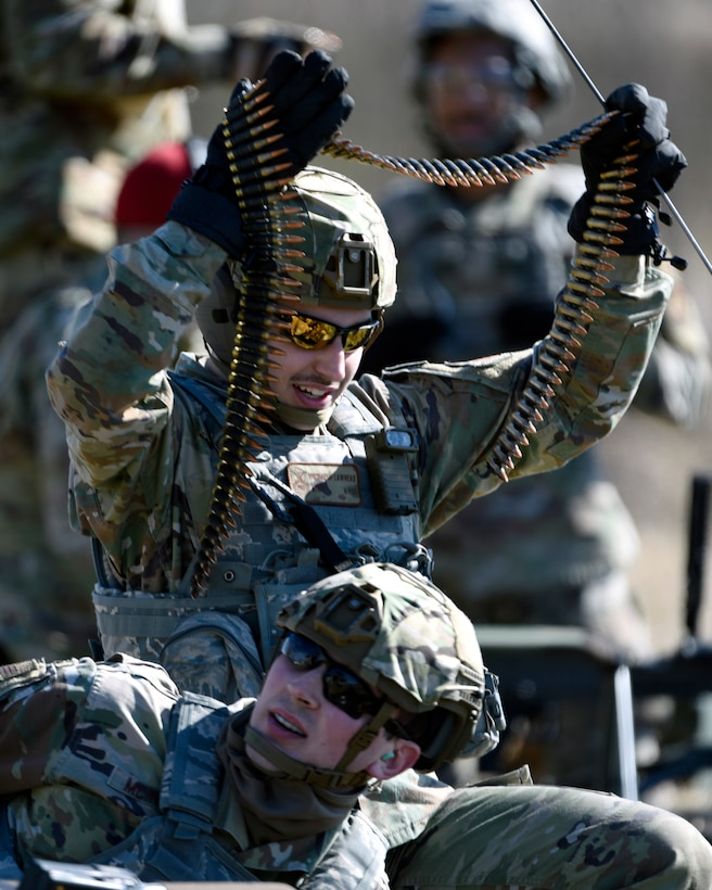 Air Force Airman 1st Class Michael Lawhead, an 88th Security Forces Squadron alarm monitor, prepares to load an M240B machine gun with Staff Sgt. Sawyer McIntyre, an 88th SFS combat arms instructor, at Camp Atterbury in Edinburgh, Indiana, on Feb. 25, 2021. The combat arms instructors, from Wright-Patterson Air Force Base, Ohio, travel to Camp Atterbury multiple times each year for readiness and qualification training with deployers on machine guns and grenade launchers. (U.S. Air Force photo by Ty Greenlees)