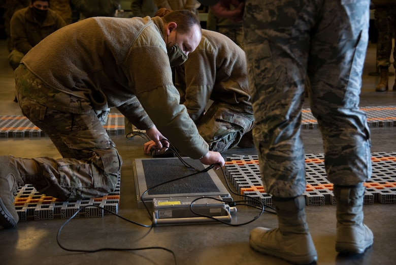 Airmen are kneeling on the ground to connecting wires to a scale