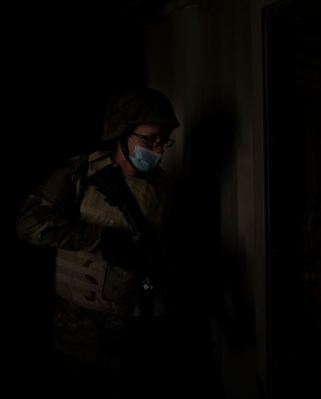 A male Airman stands ready to clear a room during tactical training.