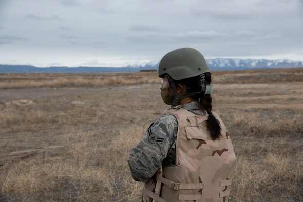 A female Airmen stands providing security for a tactical training exercise.