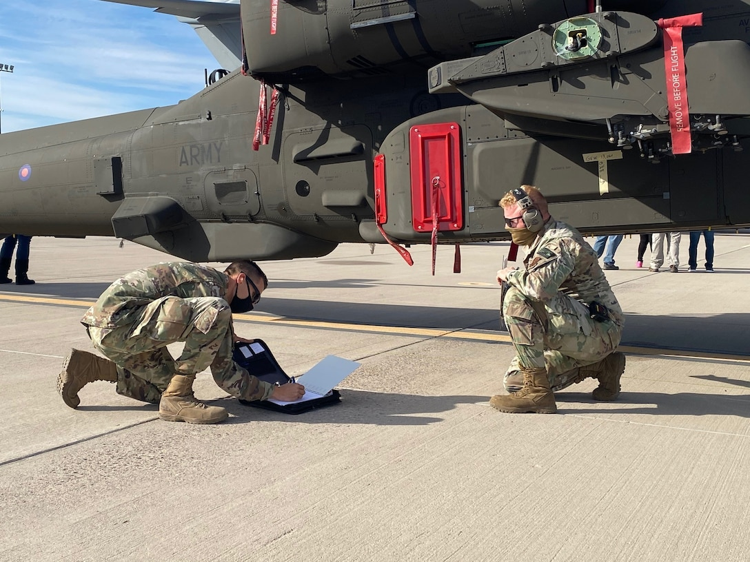 Staff Sgt. Chaz Bruno and Staff Sgt. Joe Franzen, air cargo specialists with the 161st Logistics Readiness Squadron, conduct a pre-flight inspection of an AH-64 Apache helicopter at the Goldwater Air National Guard Base in Phoenix, Arizona on Jan. 21, 2021. The 161st was contacted by the U.S. Army's Apache foreign military sales program office to help load the attack helicopters on C-17 aircraft for shipment to the UK, due to its secure ramp space for the project, and qualified air transportation specialists who can process complex air cargo ensuring safety of flight during air transport.  (U.S. Air National Guard photo by 2nd Lt. Wes Parrell)
