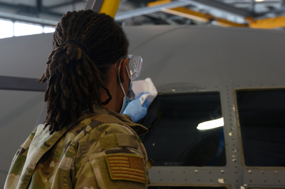 An Airman applies rubbing alcohol to a C-130J.