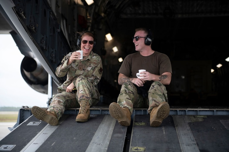 Woman and Man share take a water break on the ramp of a C-17 Globemaster