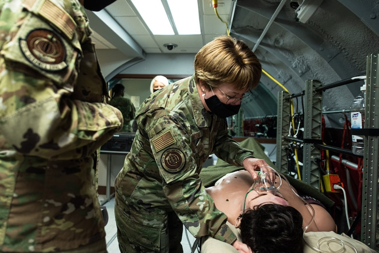 An Airmen gives care to a patient.