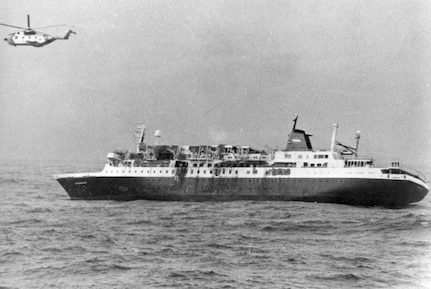 MS Prinsendam sinking with a USCG HH-3 flying above the wreck