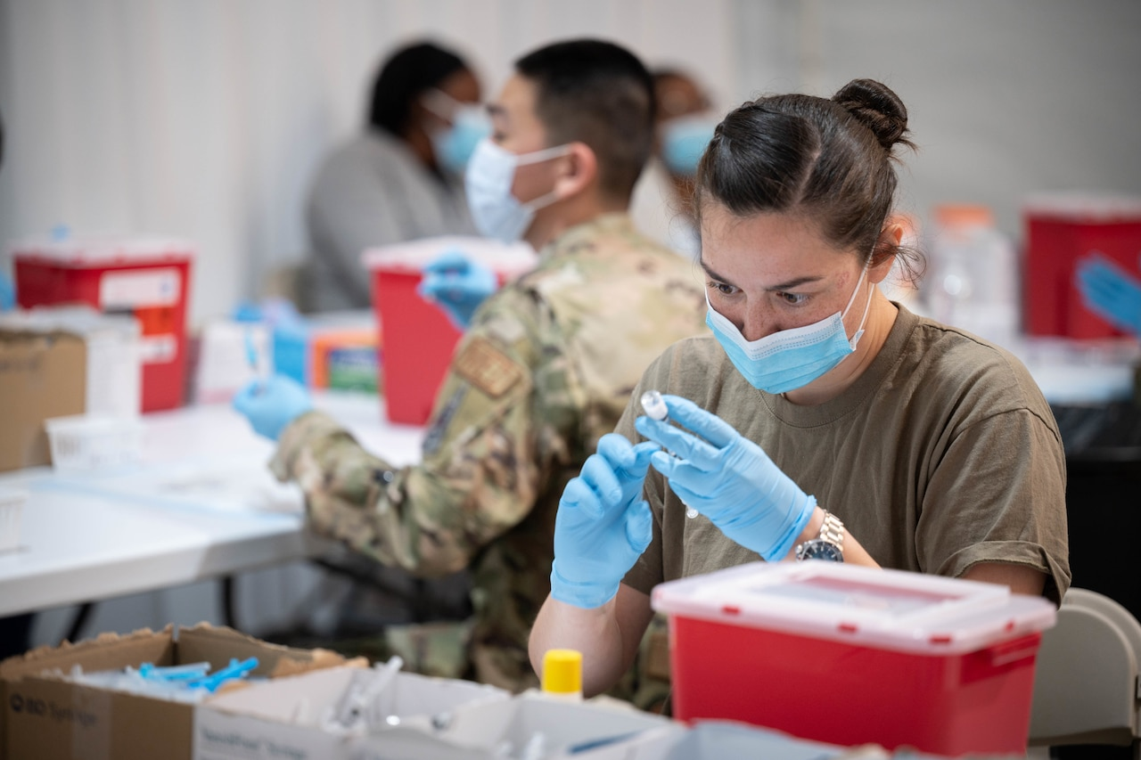 A soldier wearing a face mask and gloves holds a syringe while inserting the needle into a vial to prepare for a  COVID-19 vaccination.